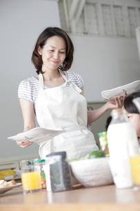 料理を運ぶエプロン姿の女性の写真素材 [FYI02933772]