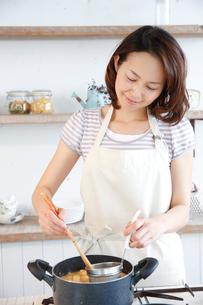 キッチンで調理をする30代女性の写真素材 [FYI02933773]