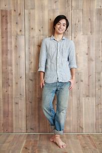 木の壁の前で微笑む若い男性の写真素材 [FYI02933779]