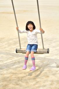 公園のブランコで遊ぶ女の子の写真素材 [FYI02933801]