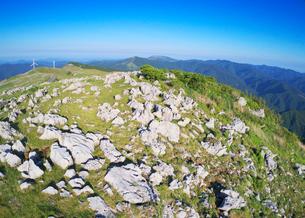 姫鶴牧場の石灰岩群と妙見森などの山並みと風力発電の風車の写真素材 [FYI02934364]