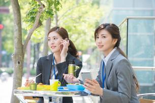 弁当を食べスマホを見て電話するOL2人の写真素材 [FYI02934448]