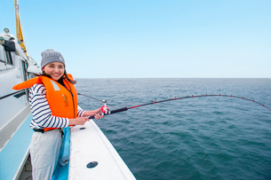 船で海釣りする20代女性の写真素材 [FYI02934458]
