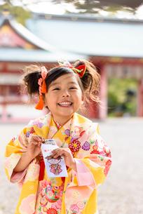 お年玉袋を見せる晴れ着を着た女の子の写真素材 [FYI02935100]