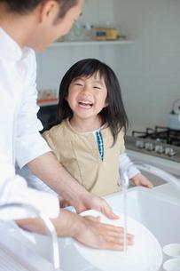 皿を洗う父親と笑顔の娘の写真素材 [FYI02935123]
