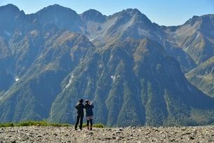 穂高連峰と撮影をしている山ガールの写真素材 [FYI02935354]