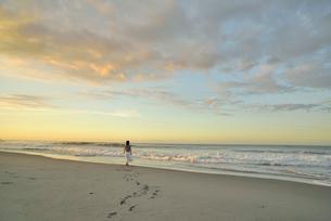 夜明けの海岸を歩く女性の写真素材 [FYI02935382]