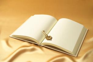 シルクの布に置かれた白紙の本の写真素材 [FYI02935417]