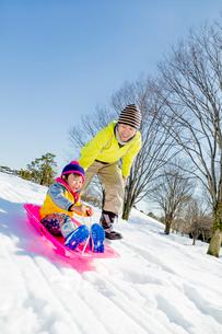 雪の公園でソリ遊びをする父と息子の写真素材 [FYI02935838]