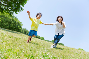 公園で手をつないで遊ぶ母と息子の写真素材 [FYI02935840]