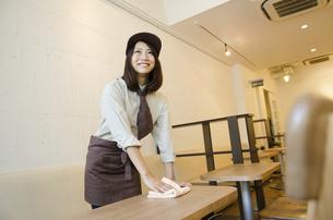 制服を着てテーブルを拭く女性の写真素材 [FYI02935867]