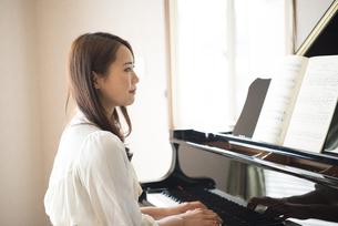 楽譜を見ながらピアノを弾いている女性の写真素材 [FYI02935892]
