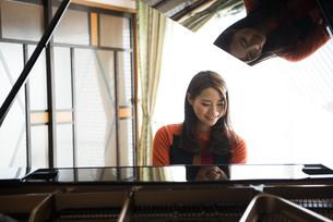 部屋でグランドピアノを弾いている女性の写真素材 [FYI02935908]