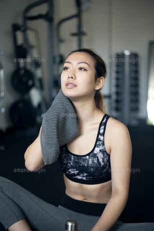 ジムで汗を拭きながら休憩をしている女性の写真素材 [FYI02935909]