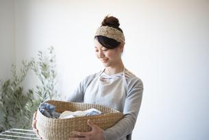 洗濯物の入ったかごを持っている女性の写真素材 [FYI02935920]