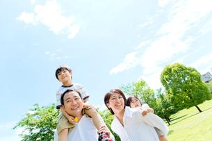 公園を歩く4人家族の写真素材 [FYI02935945]