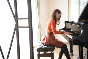 部屋でピアノを弾いている女性の写真素材 [FYI02936103]