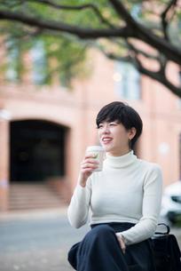 コーヒーを持って微笑んでいる女性の写真素材 [FYI02936142]