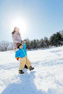 雪の公園で手をつないで歩く母親と息子の写真素材 [FYI02936164]