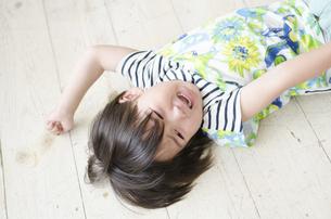 床に転がって泣いている男の子の写真素材 [FYI02936171]