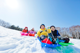 雪の公園でソリ遊びをする子供たちの写真素材 [FYI02936174]