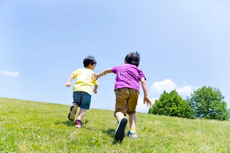 公園を走る男の子2人の後ろ姿の写真素材 [FYI02936252]