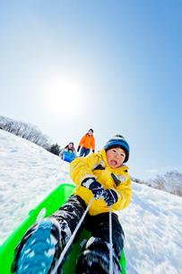 雪の公園でソリ遊びをする親子の写真素材 [FYI02936292]