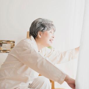 ベッドに座りカーテンを開けるシニア女性の写真素材 [FYI02936342]