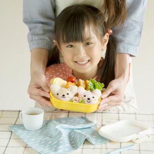 ウサギのキャラクター弁当を持ち微笑む女の子の写真素材 [FYI02936349]