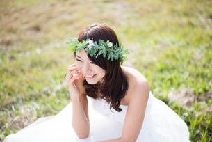 草の上に座るウェディングドレス姿の女性の写真素材 [FYI02936389]