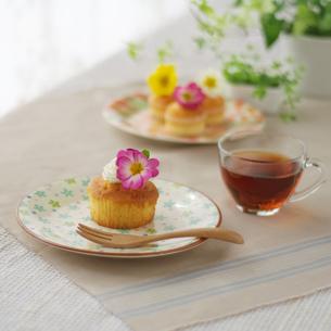 花を飾ったカップケーキのあるティータイムの写真素材 [FYI02936428]