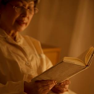 ベッドで本を読むシニア女性の写真素材 [FYI02936447]