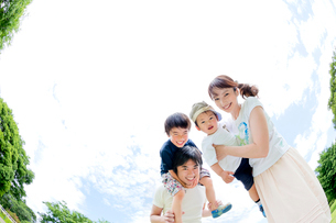 公園で遊ぶ4人家族の写真素材 [FYI02936486]