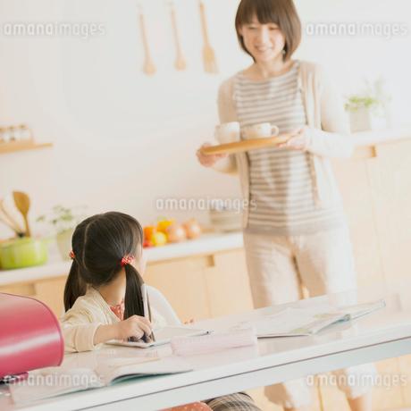 勉強をする女の子と飲み物を運ぶ母親の写真素材 [FYI02936498]