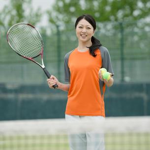 テニスラケットを持ち微笑むミドル女性の写真素材 [FYI02936515]