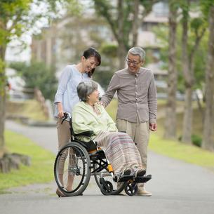 車椅子に乗る母と散歩をする父娘の写真素材 [FYI02936520]