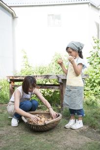 収穫した玉ねぎを持っている女性と子供の写真素材 [FYI02936528]