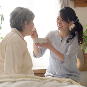 母におかゆを食べさせる娘の写真素材 [FYI02936548]