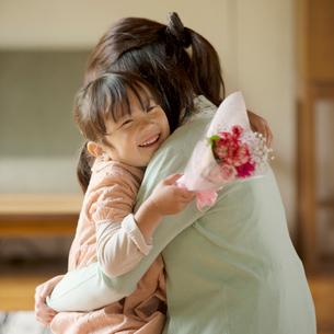 母親に花束を渡す女の子の写真素材 [FYI02936550]