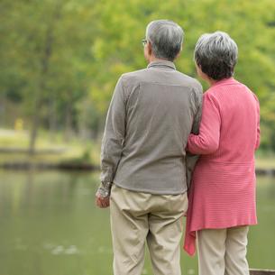 湖を眺めるシニア夫婦の後姿の写真素材 [FYI02936555]