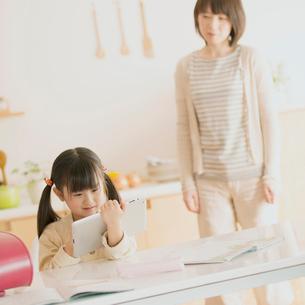 タブレットPCで勉強をする女の子と母親の写真素材 [FYI02936577]