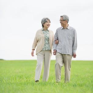草原を歩くシニア夫婦の写真素材 [FYI02936593]
