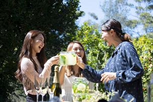 ガーデンパーティで乾杯をしている笑顔の女性3人の写真素材 [FYI02936648]