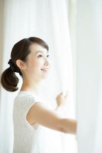 カーテンを開ける女性の写真素材 [FYI02936698]