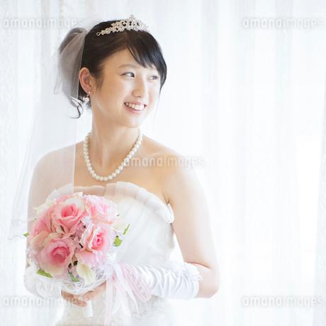 ブーケを持ち微笑む花嫁の写真素材 [FYI02936722]