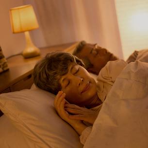 ベッドで眠るシニア夫婦の写真素材 [FYI02936736]