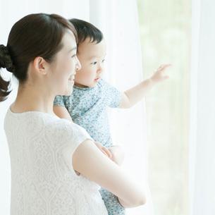 子供を抱き窓の外を眺める母親の写真素材 [FYI02936738]