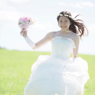 草原でブーケを持ち微笑む花嫁の写真素材 [FYI02936753]