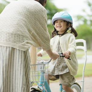 自転車に乗る女の子と母親の写真素材 [FYI02936850]