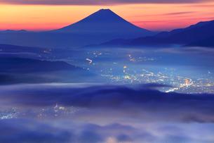 高ボッチ高原より夜明けの富士山と諏訪の街明かりに雲海の写真素材 [FYI02936896]